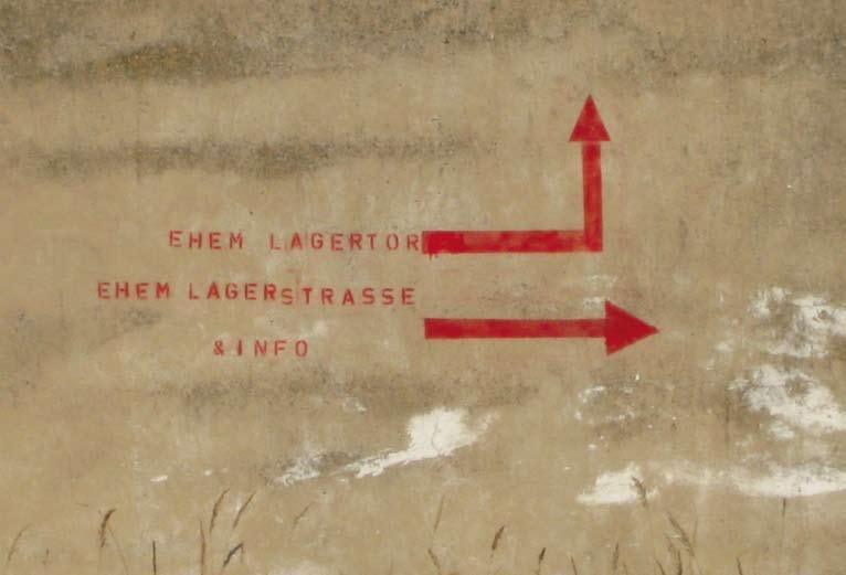 """Wegweiser an einer Wand: """"Ehemaliges Lagertor, ehemalige Lagerstraße & Info"""""""
