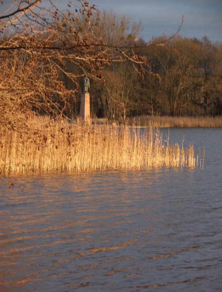 Teich neben dem ehemaligen KZ Ravensbrück in der Abendsonne, im Hintergrund ein Denkmal