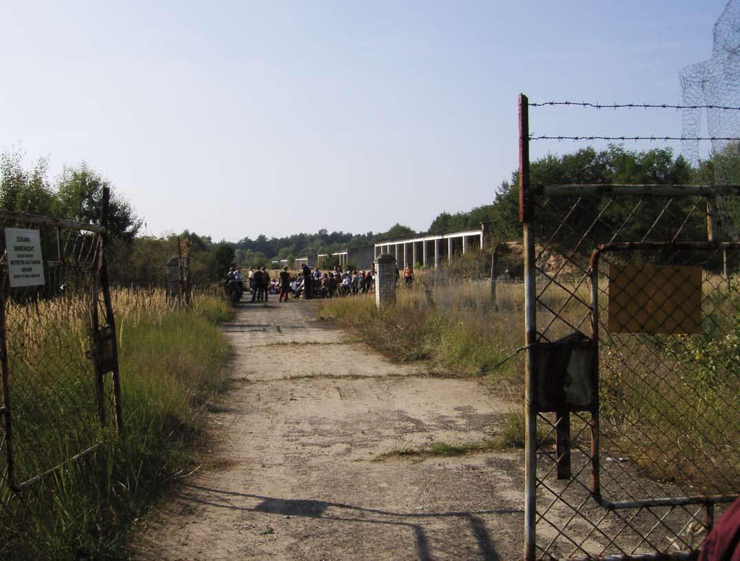 Blick durch das Tor zum Lager auf eine Versammlung auf dem Gelände