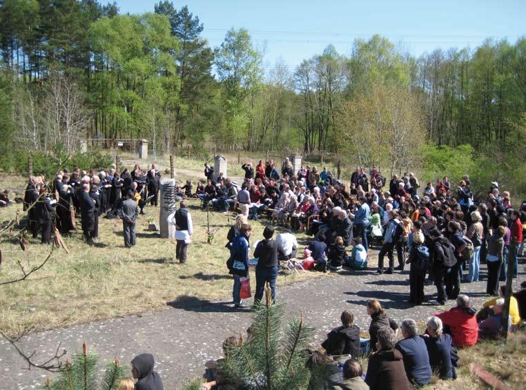 Eine Gedenkveranstaltung auf dem Gelände. Ungefähr 120 Menschen haben sich um einen Gedenkstein versammelt.