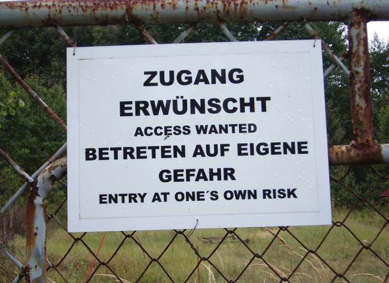 """Schild auf dem Tor: """"Zugang erwünscht. Betreten auf eigene Gefahr"""""""