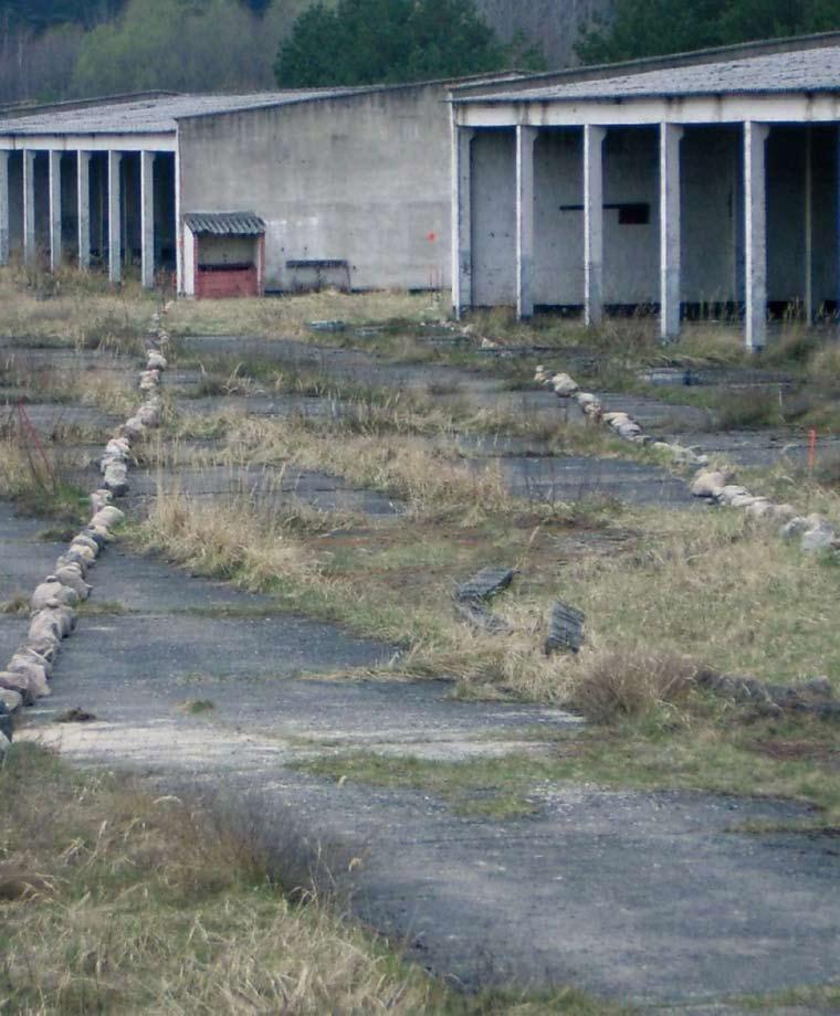 Mit Steinen ist der Grundriss der ehemaligen Baracken auf dem Gelände des KZ Uckermark aufgelegt. Im Hintergrund die Ruinen der Garagen der Roten Armee.