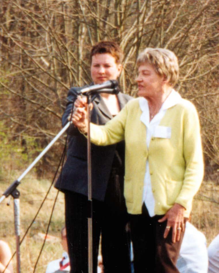 Eine ältere Dame mit gelber Weste spricht in ein Mikrofon.