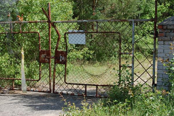 Das Tor zum Gelände; im Maschendraht ist ein großes Loch.